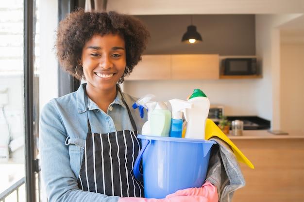 Afro mulher segurando um balde com itens de limpeza.