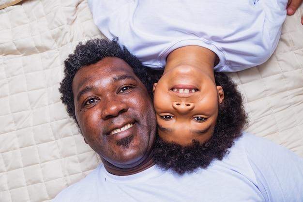 Afro pai e filho deitados na cama