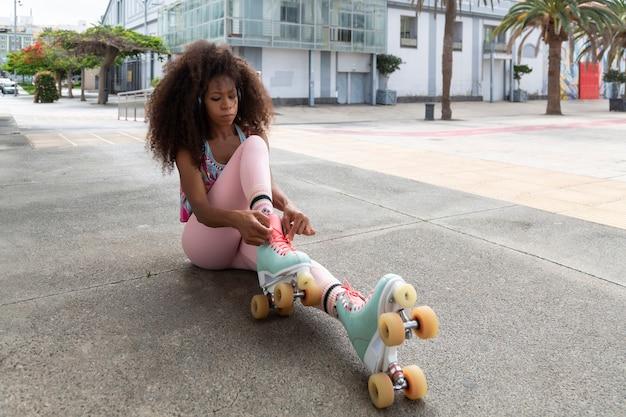 Afro skatista sentada amarrando seus patins