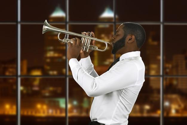 Afro trompetista tocando música.