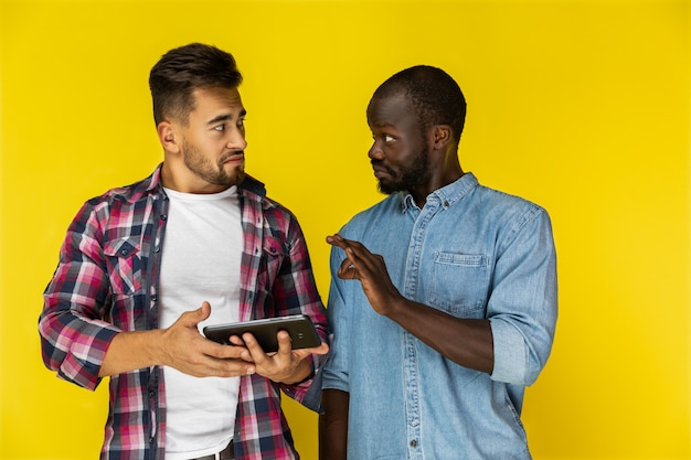 Afroamerican guy está provando algo para europeu guy em camisas informais