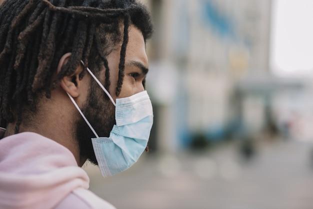 Afroamerican masculino vestindo máscara médica