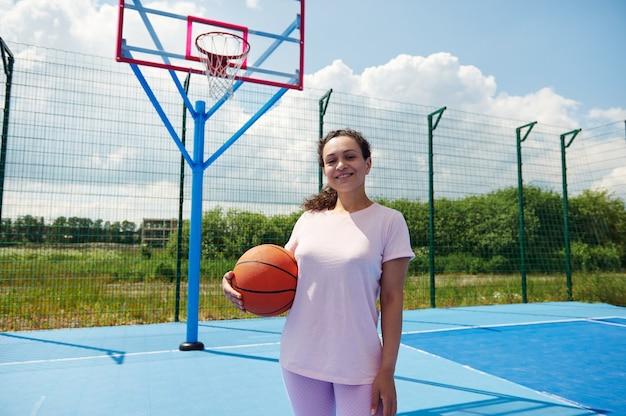 Afroamericana jogadora de basquete em pé em um parquinho e sorrindo segurando uma bola de basquete sob o braço