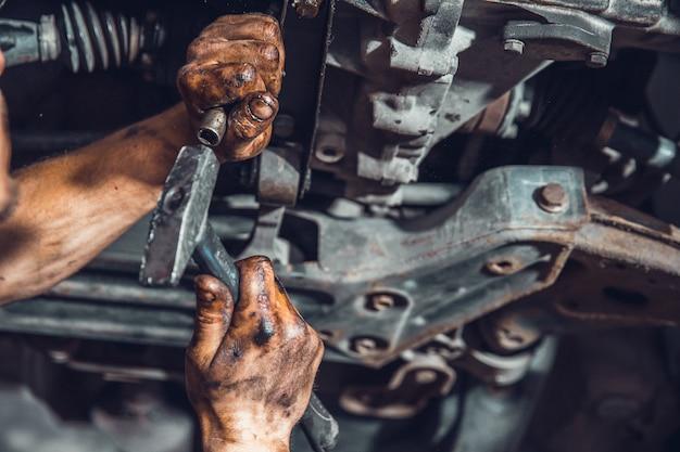 Afrouxando o parafuso no carro durante o reparo no serviço com a ajuda do ajustador e do martelo