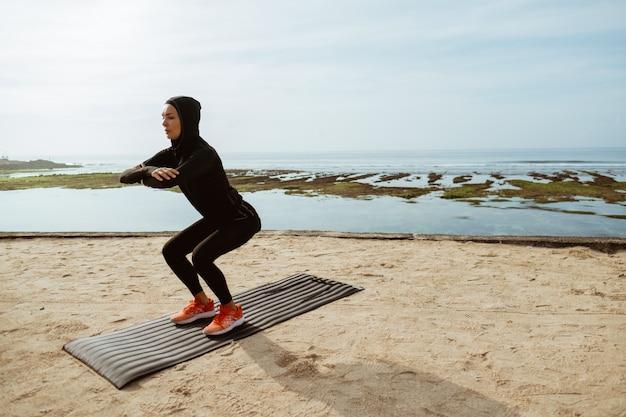 Agachamento, mulher muçulmana de esporte de cócoras