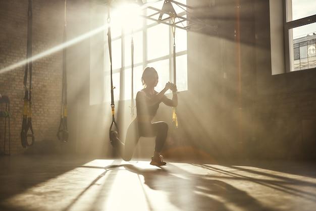 Agachamento profundo de comprimento total de jovem atlética em roupas esportivas, treinando pernas com trx fitness