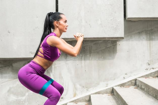 Agachamentos. jovem mulher desportiva da faixa da resistência que faz o exercício da ocupa com a faixa do montante que estica a correia. trens de fitness feminino
