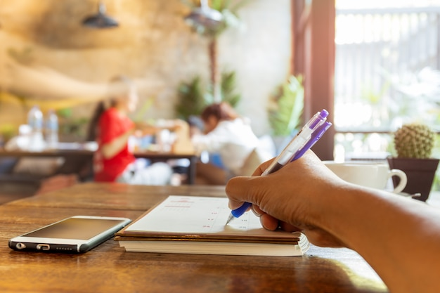Agenda da escrita da mão do empresário no diário do calendário com a pena na tabela.