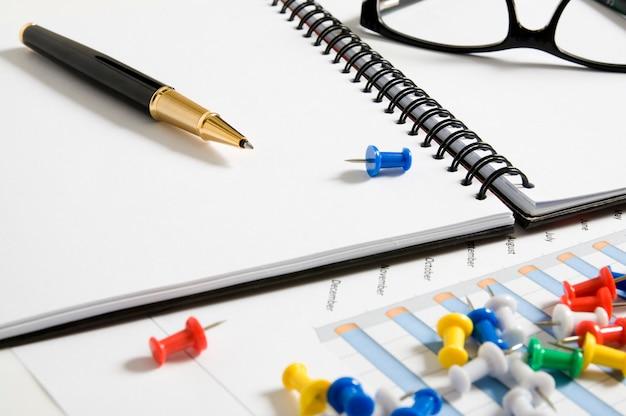 Agenda em branco com caneta, óculos, papel de relatório e pinos
