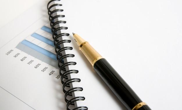 Agenda em branco e uma caneta. alguém quer analisar o relatório de negócios