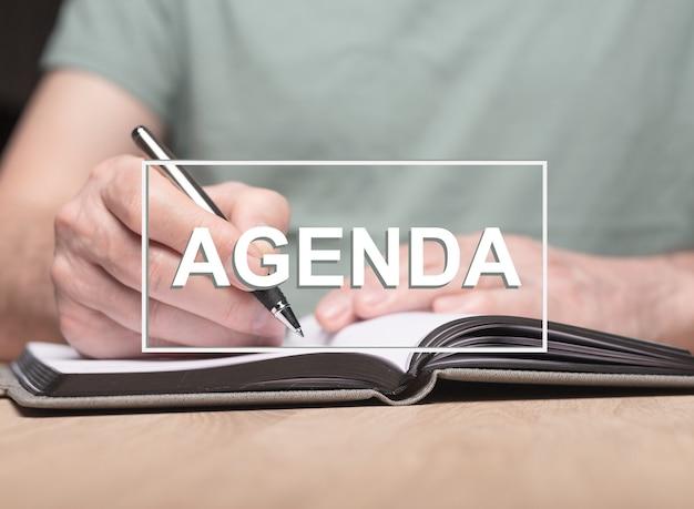 Agenda palavra com foto de mãos masculinas, escrevendo no planejador ou organizador.
