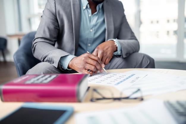 Agendando reunião. close-up de um empresário sentado perto da agenda enquanto programa uma reunião com o parceiro