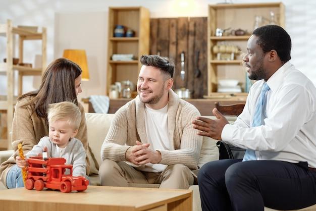 Agente afro-americano conversando com jovem casal com filho sobre hipoteca de imóveis
