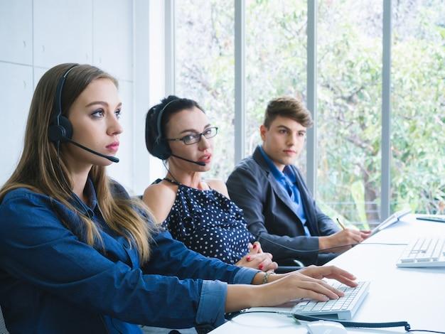 Agente amigável da equipe do operador com fones de ouvido trabalhando em um call center