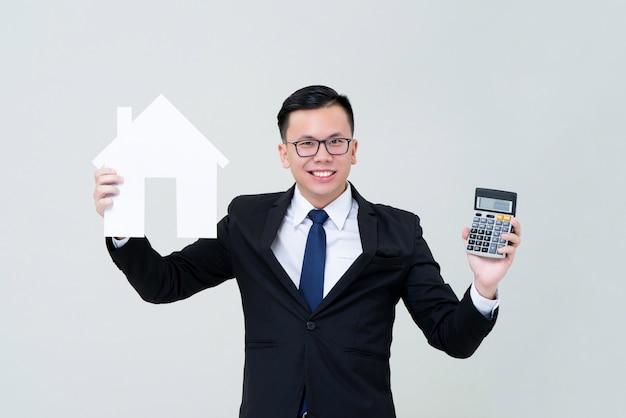 Agente asiático do homem que mostra o modelo da casa com calculadora