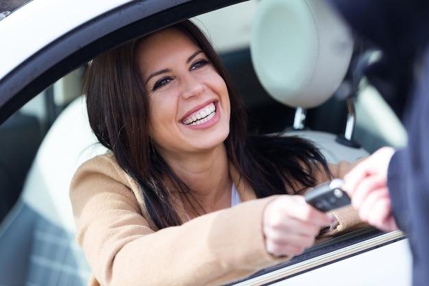 Agente da agência de aluguel de carros que dá as chaves do carro para uma jovem bonita.