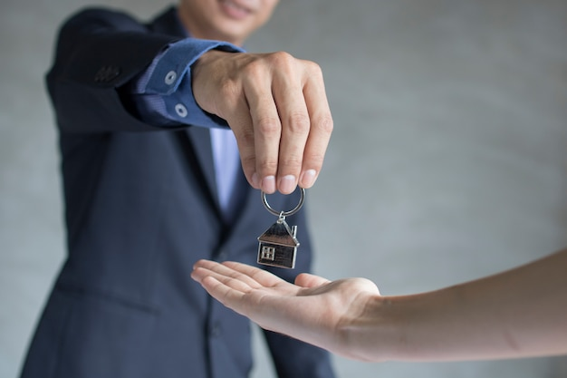 Agente da casa e imóveis tomam a chave para os proprietários