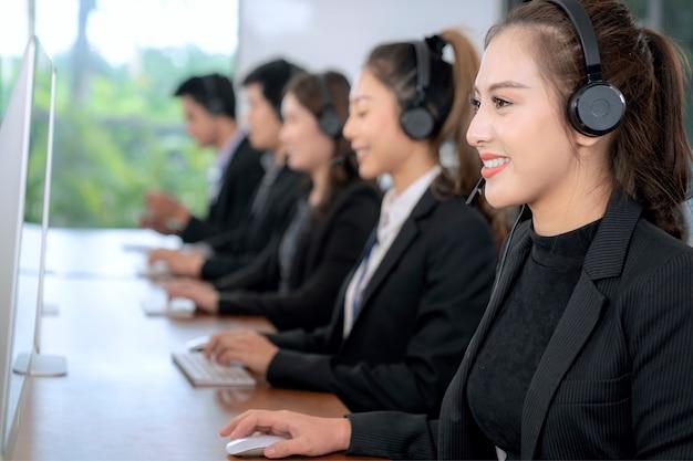 Agente de atendimento ao cliente asiática positiva com fone de ouvido, trabalhando em uma empresa de call center