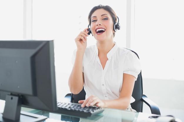 Agente de call center alegre sentado em sua mesa em uma chamada