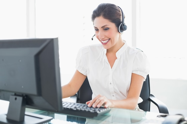 Agente de call center alegre trabalhando em sua mesa em uma chamada