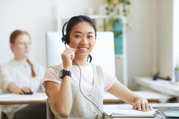 Agente de call center asiático usando fone de ouvido e sorrindo, trabalhando no atendimento ao cliente