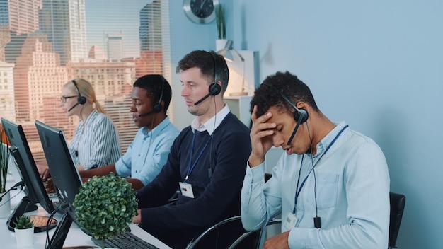 Agente de call center multiétnico insatisfeito, conversando com o cliente no telefone