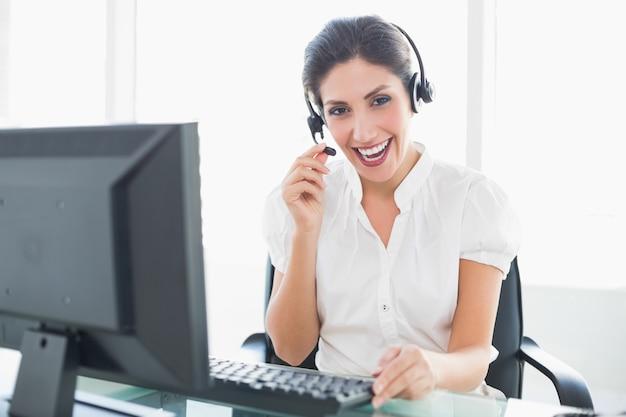 Agente de centro de chamada feliz sentado em sua mesa em uma chamada