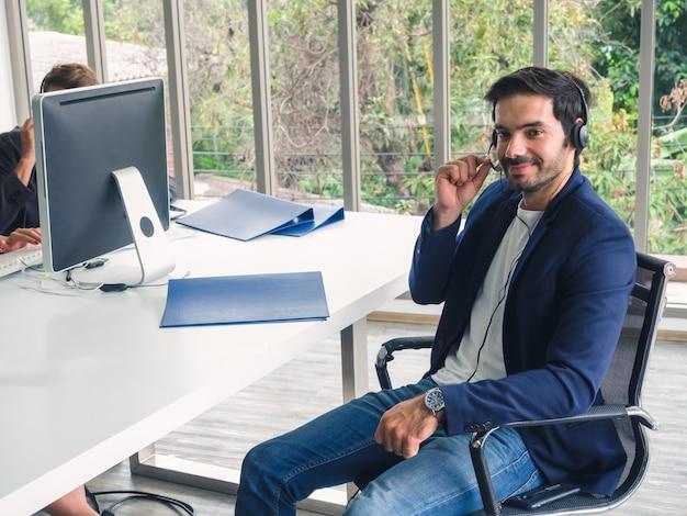 Agente de homem amigável operador com fones de ouvido trabalhando em um call center