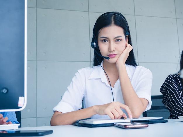 Agente de mulher amigável operador com fones de ouvido trabalhando em um call center