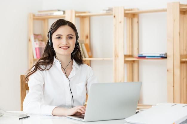 Agente de mulher jovem operador amigável ou mulher de negócios com fones de ouvido trabalhando em um call center.