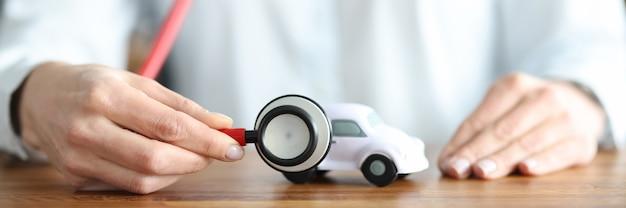 Agente de seguros de mulher ouvindo com estetoscópio um carro de brinquedo close-up