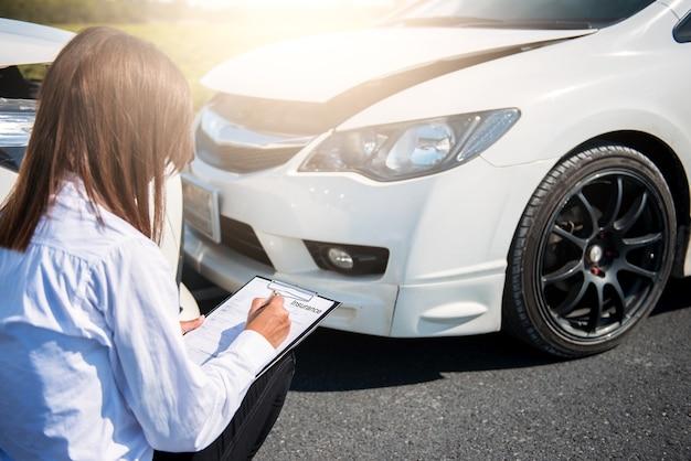 Agente de seguros, escrevendo na área de transferência após carros de acidente