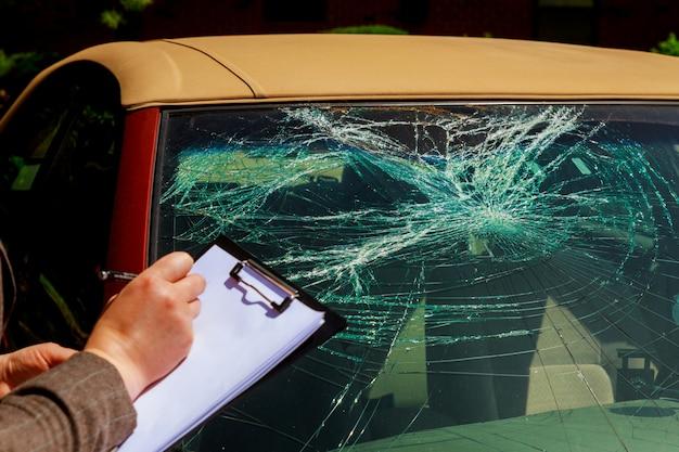 Agente de seguros, escrevendo na área de transferência, relatório de acidente de carro