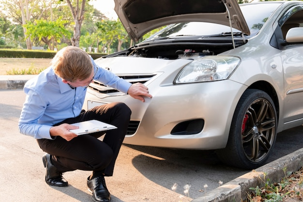Agente de seguros, escrevendo o documento na prancheta, examinando o carro após acidente, conceito de seguro