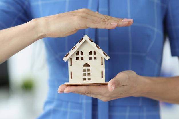 Agente de seguros feminino está segurando o conceito de seguro imobiliário de casa de madeira