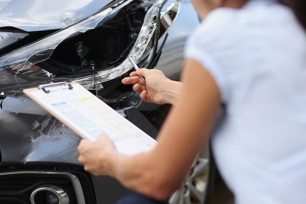 Agente de seguros inspeciona danos ao carro após o acidente, obtendo seguro após um acidente
