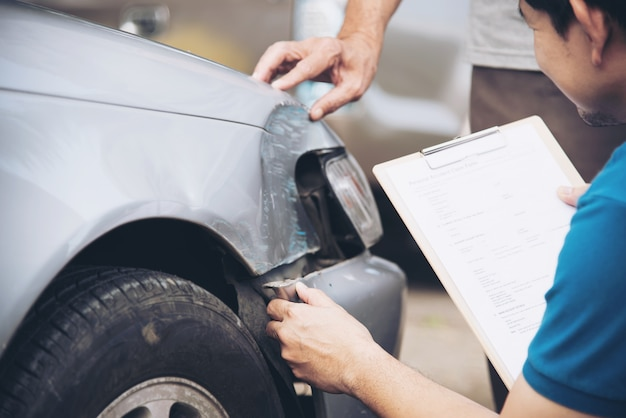 Agente de seguros que trabalha durante processo de reivindicação de acidente de carro no local, reclamação de seguro de pessoas e de carro