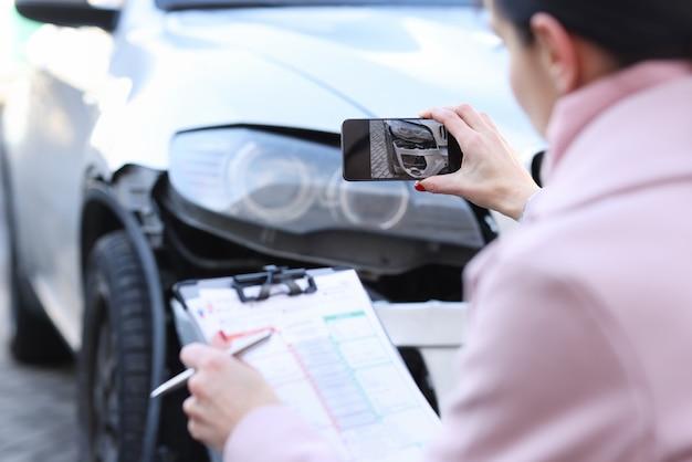 Agente de seguros tirando fotos do carro destruído closeup. estimativa de custo do conceito de carro danificado