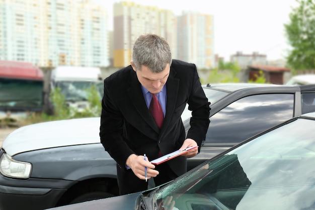 Agente de seguros verificando carro quebrado após acidente