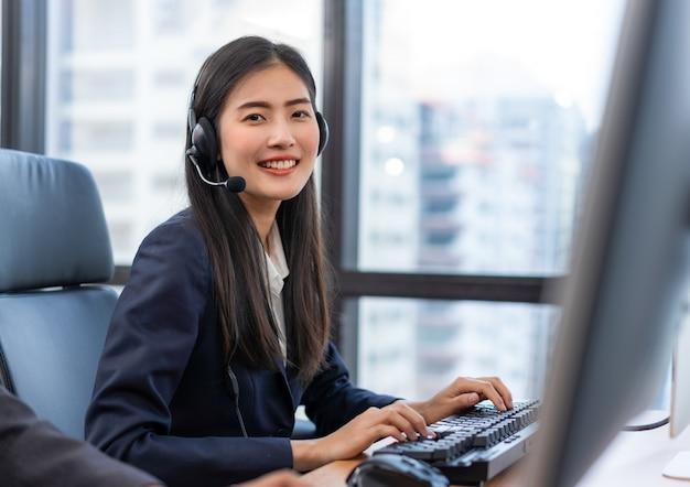 Agente de serviço ao cliente de mulher asiática sorridente feliz operador com fones de ouvido