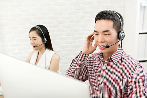 Agente de serviço ao cliente de telemarketing masculino asiático sorridente, trabalhando em call center