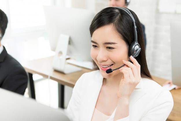 Agente de serviço ao cliente de telemarketing mulher asiática bonita sorridente, trabalhando em call center