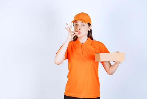 Agente de serviço feminino com código de vestimenta cor de laranja segurando uma caixa de papelão e mostrando sinal de sucesso