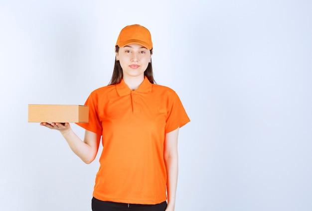 Agente de serviço feminino com dresscode cor de laranja segurando uma caixa de papelão