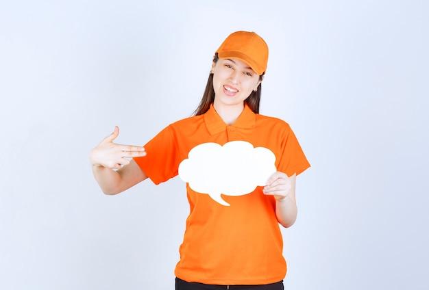 Agente de serviço feminino com dresscode cor laranja segurando um quadro de informações em forma de nuvem