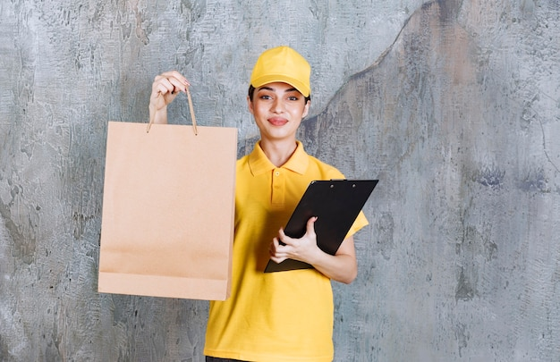 Agente de serviço feminino de uniforme amarelo, segurando um saco de papel e uma lista negra de endereços.