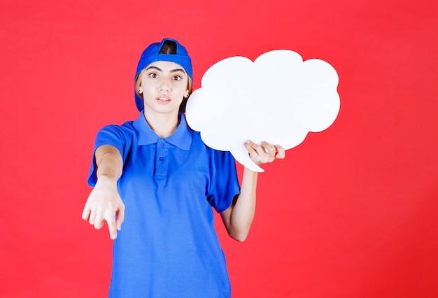 Agente de serviço feminino de uniforme azul, segurando um balcão de informações de forma de nuvem e convidando alguém.