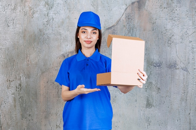 Agente de serviço feminino de uniforme azul, segurando uma caixa de papelão aberta.