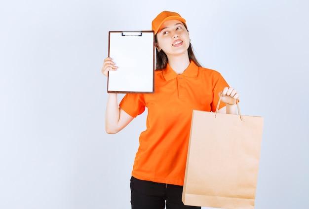 Agente de serviço feminino em dresscode cor laranja, segurando uma sacola de compras de papelão e apresentando a lista de assinaturas para o cliente, enquanto olha pensativa.