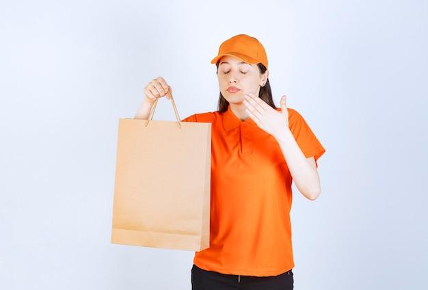 Agente de serviço feminino em dresscode cor laranja, segurando uma sacola de compras de papelão e cheirando o produto dentro.